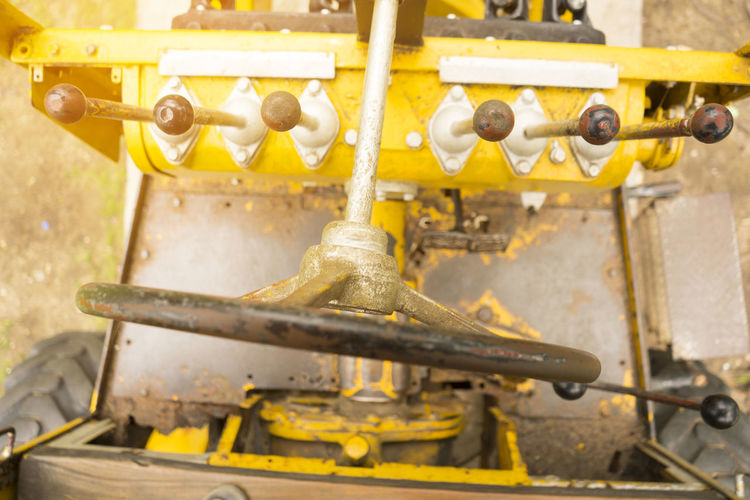 The old machinery for digging the ground in the ground. Agricultural Machinery Business Close-up Control Conveyor Belt Day Equipment Factory Industrial Equipment Industry Machine Part Machine Valve Machinery Manufacturing Equipment Metal Mode Of Transportation No People Old Production Line Road Machinery Steering Wheel Technology Transportation Valve Yellow