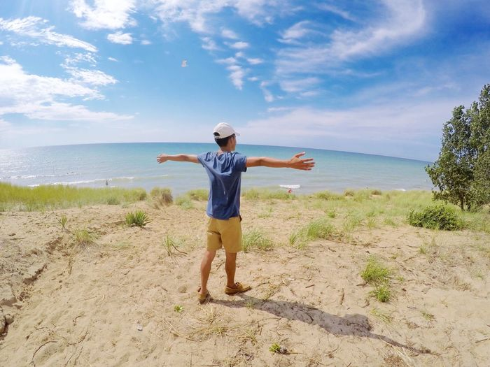 Rear view of young man with arms outstretched standing at beach against sky during sunny day