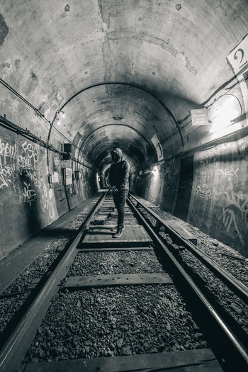 Rear view of man standing on railroad tracks in tunnel