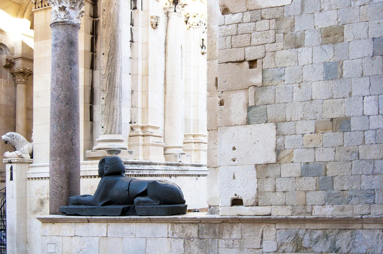 Statue of sphinx on stone ledge