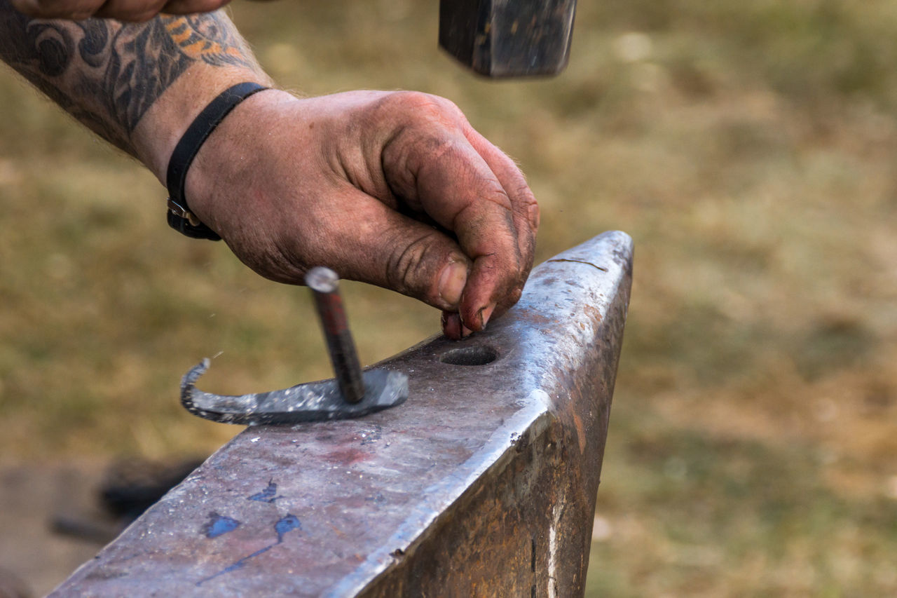 Cropped Hand Of Man Working On Metal