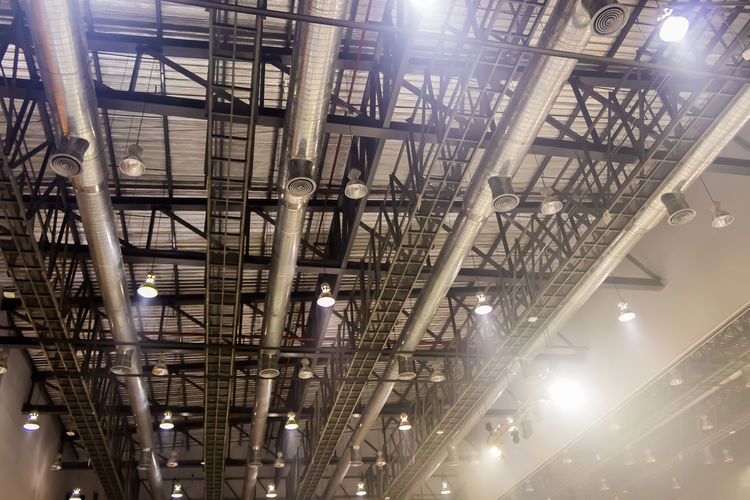 Low angle view of illuminated lights hanging on ceiling in building