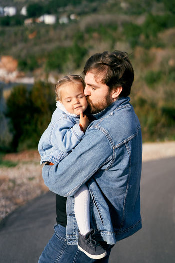 Father kissing daughter while standing on road