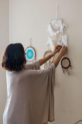 Woman decorating wall at home