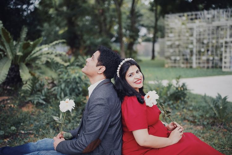 Portrait of happy pregnant woman sitting with boyfriend at park