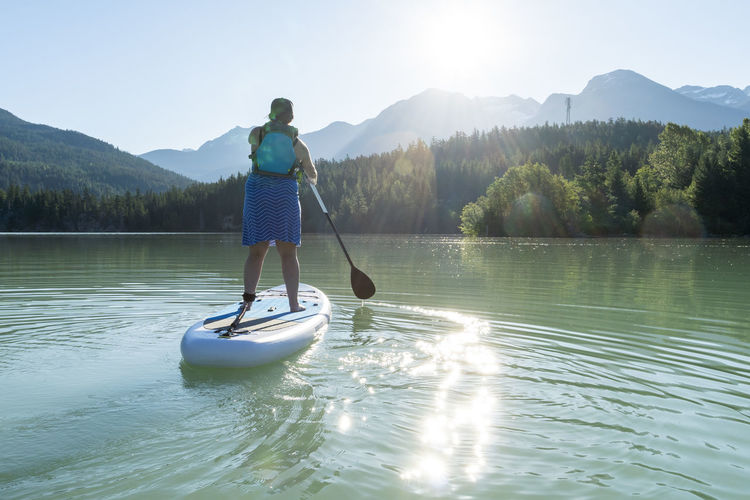 Man surfing on lake against sky