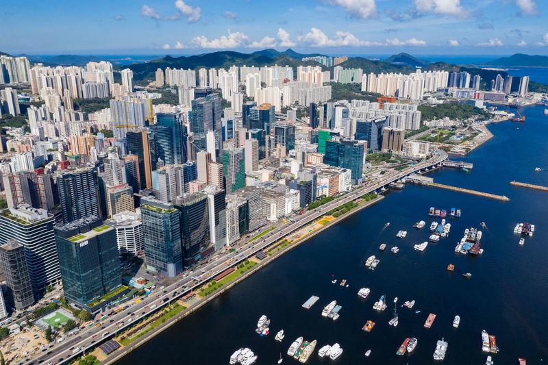 Aerial view of modern buildings by sea against sky