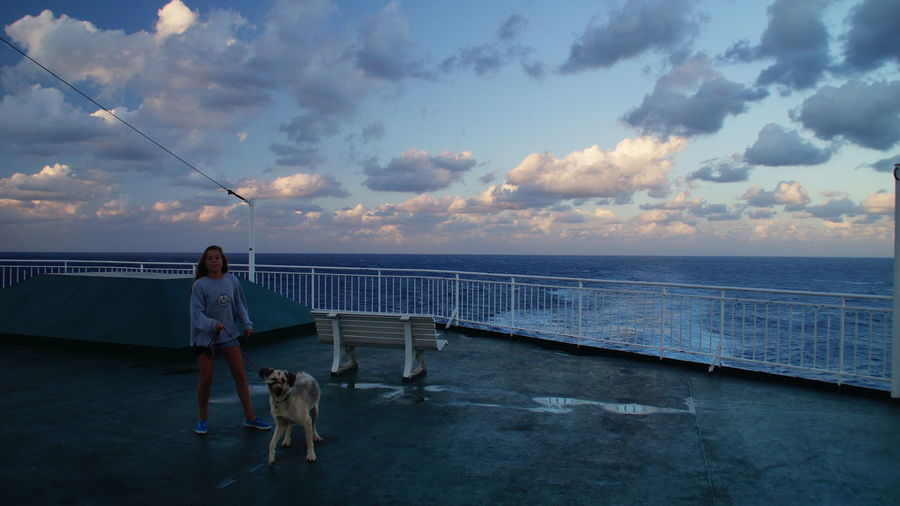 Full length of girl with dog standing at promenade by sea against sky