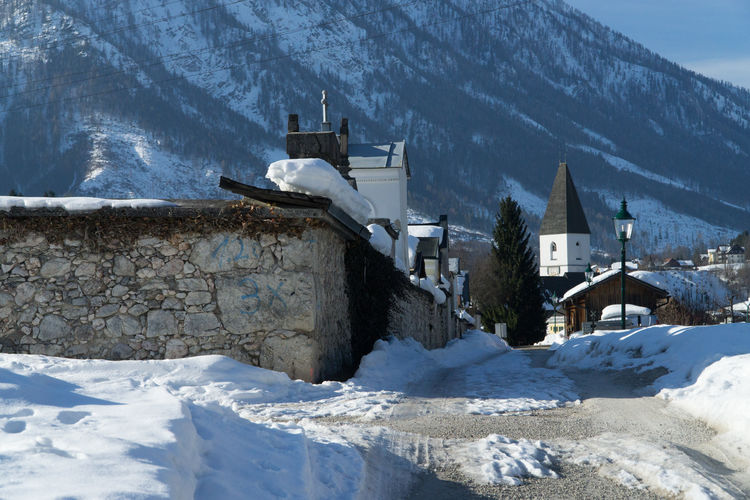 Snow covered houses by buildings against mountains
