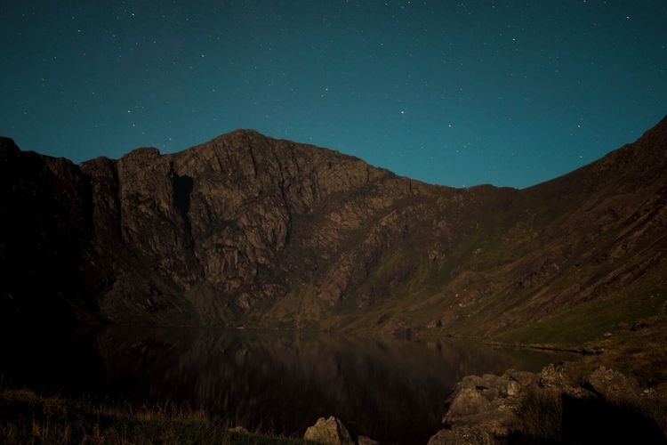 Scenic view of rocky mountains against sky at night