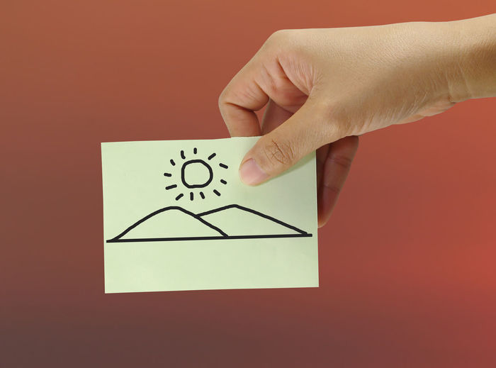 Hand of a people holding a paper note with drawing mountain and sun for concept of environmental protection. Environmental Hand Rail Holding Hands Protection Of Nature Sunlight Sunny Concept Conceptual Drawing Drawings Environmental Conservation Environmental Issues Hand Holding Mountain Mountains Mountains And Sky Paper Note Paper Notes Protection Sky Sun Sunset