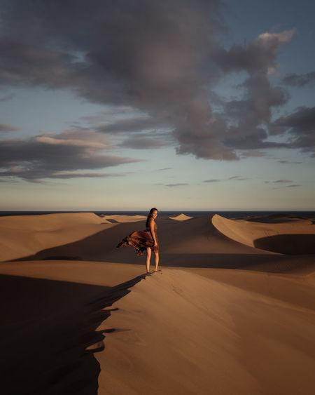 Woman on sand dune against sky
