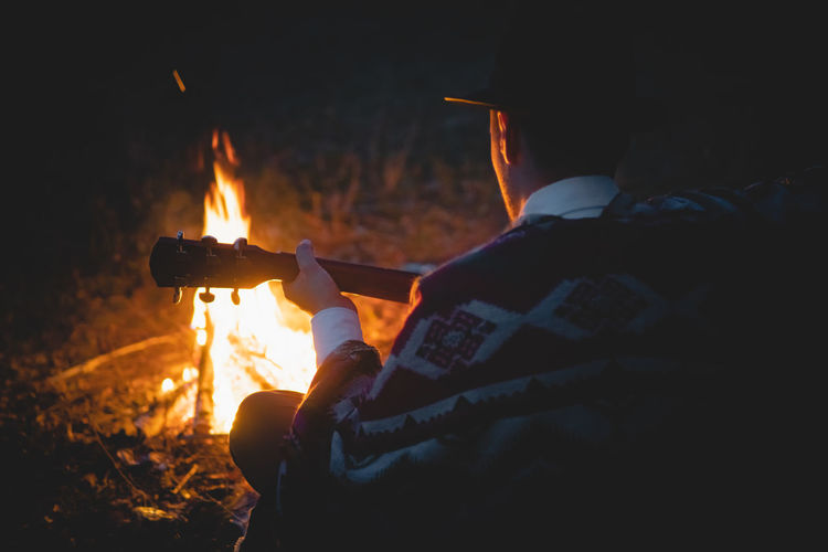 Rear view of man with guitar sitting by bonfire in forest