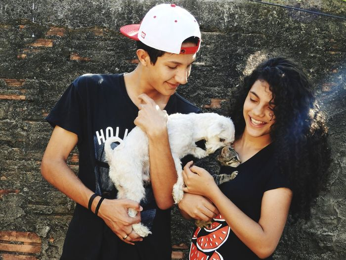 Teenage Couple With Dog And Kitten Standing Against Wall