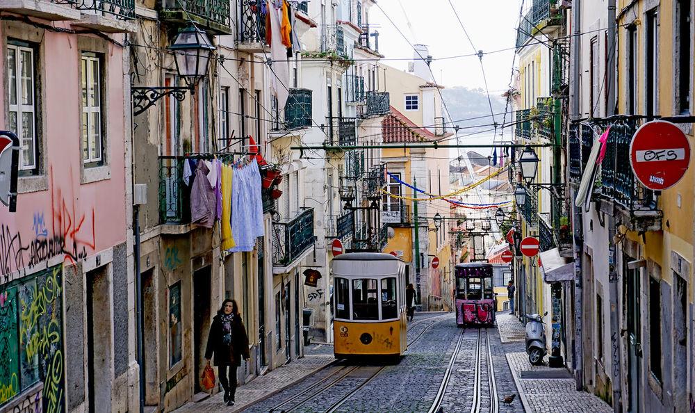 a woman walking in Lisbon, Portugal Architecture City Colorful Laundry Lisbon The Street Photographer - 2017 EyeEm Awards Tram Transportation Walking Woman
