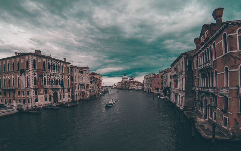 View of canal grande in venice against cloudy sky
