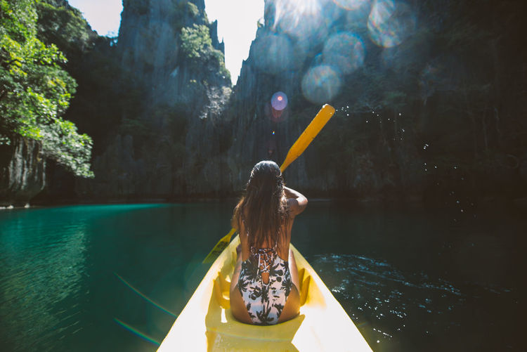 Rear view of woman kayaking in sea