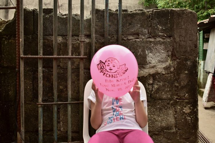 Low section of girl standing with pink balloons