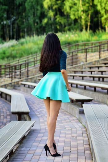 Rear view full length of young woman standing by bleachers at amphitheater
