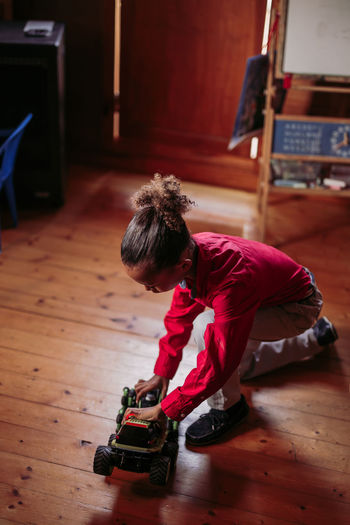 High angle view of boy playing on hardwood floor at home