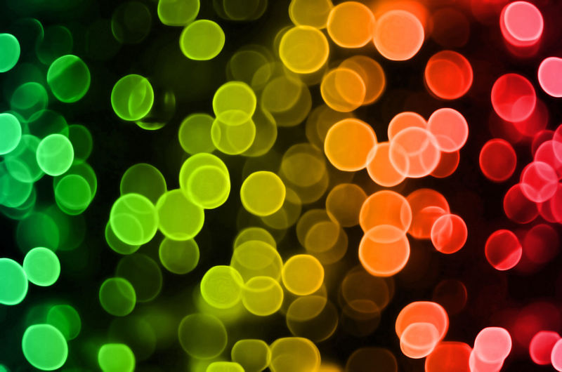 Defocused image of multi colored illuminated lights against black background