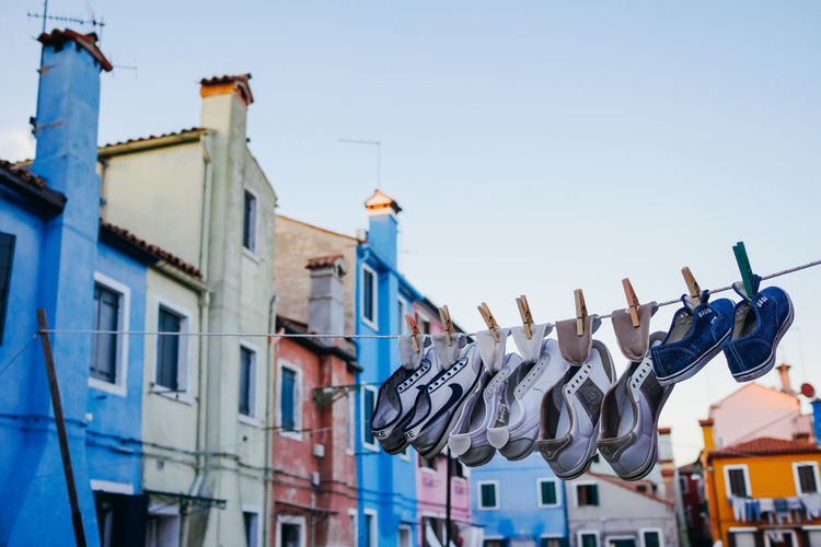 Low angle view of shoes drying on clothesline against building sky