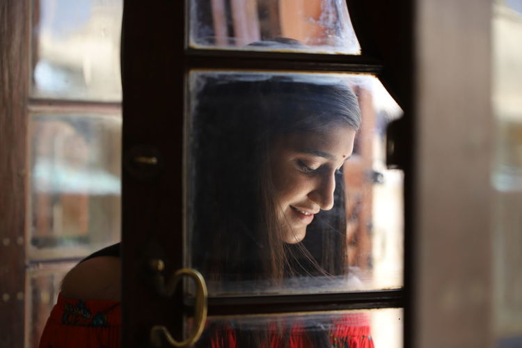 Smiling Young Woman Looking Down Seen Through Glass Window