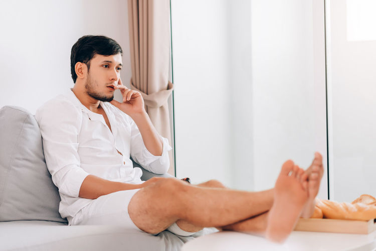 Young man looking away while sitting on bed at home