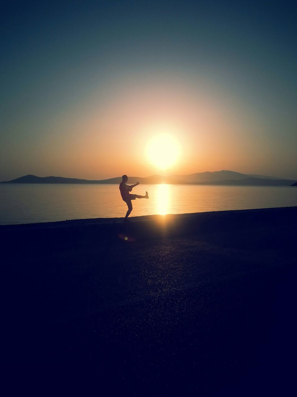 sunset, silhouette, sea, water, scenics, nature, real people, full length, one person, beauty in nature, outdoors, sun, leisure activity, horizon over water, tranquil scene, tranquility, lifestyles, skill, beach, sport, sky, clear sky, men, day, people