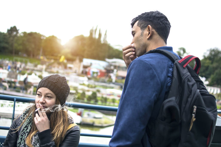 DEN HAAG, Netherlands - October 11, 2017: Woman is smoking cigarette with a lot of smoke around and man is covering his face Smoking Passive Cigarette  Smoke Woman Lungs Smell Face Nose Tobacco Female Concept Addiction Toxic person Smoker Adult Man Hand Bad Unhealthy Fingers Damage Habit Nicotine Breathe Male People Healthy Lifestyle Two Den Haag Netherlands Europe Around Covering Leisure Activity Two People Lifestyles Togetherness Emotion Outdoors
