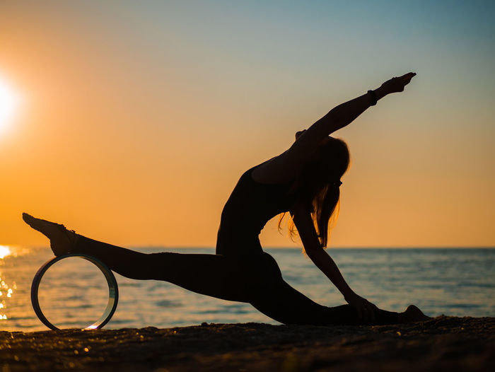 Silhouette Woman Doing Yoga At Beach Against Sky