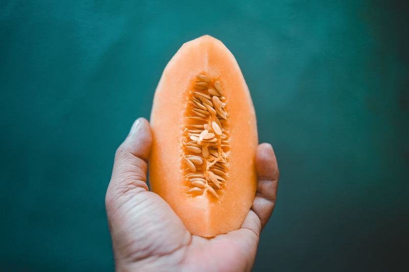 Human Hand Hand Holding Human Body Part Food And Drink One Person Food Wellbeing Personal Perspective Freshness Healthy Eating Unrecognizable Person Body Part Orange Color Fruit Lifestyles Human Finger Real People Close-up Finger Turquoise Colored Honey Dew Stone Melon