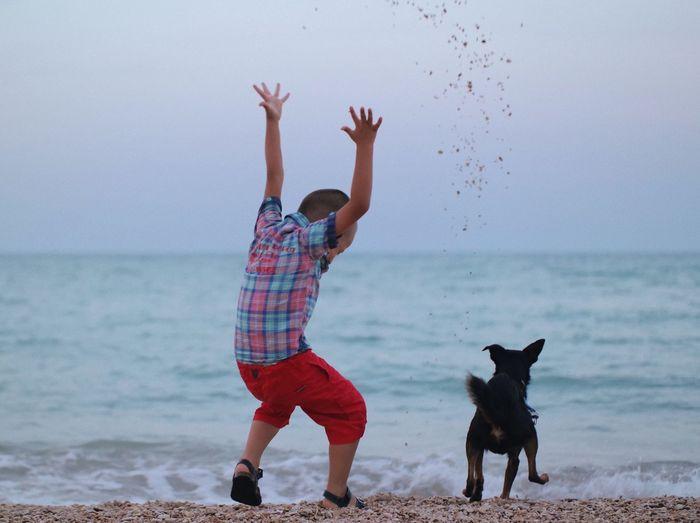 Full Length Of Boy And Dog On Beach Against Sky