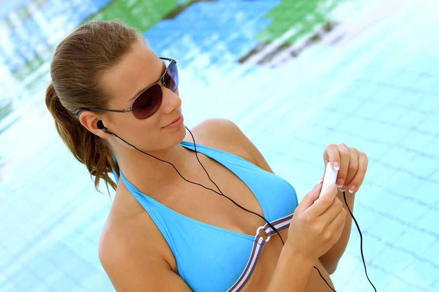 young blond woman listening to music with MP3 players at the pool Beautiful Happy Holiday Listening Music Music Summer Holidays Woman Bikini Blond Girl Happyness Leisure Leisure Activity Lifestyles Mp3 Player Pretty Relaxation Sunglasses Swimming Pool Swimwear Vacation Water Wellbeing Young Adult Young Women
