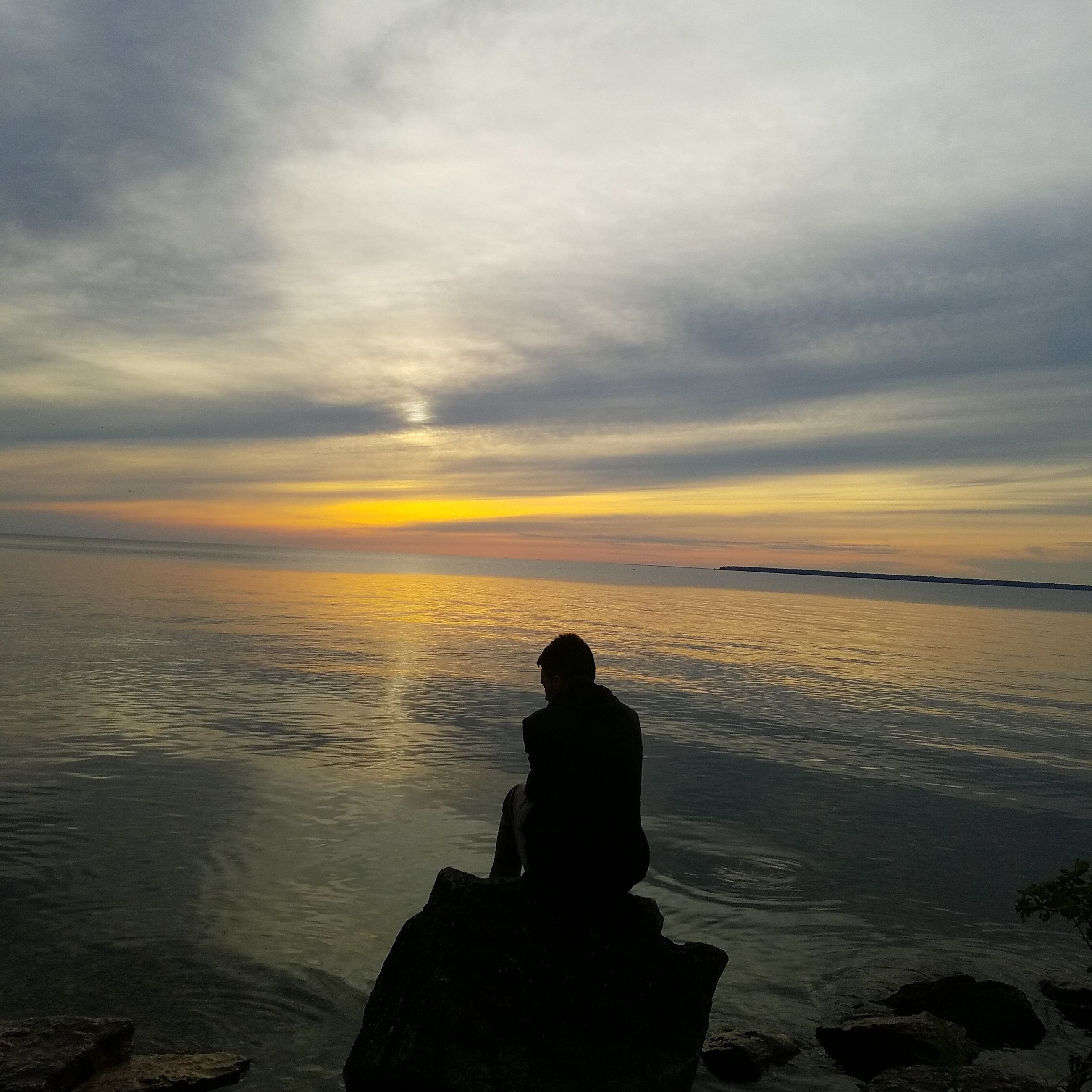 sunset, water, sea, tranquil scene, scenics, silhouette, beach, vacations, men, tourism, leisure activity, tranquility, beauty in nature, travel, lifestyles, cloud - sky, tourist, non-urban scene, nature, getting away from it all, atmosphere, travel destinations, rock - object, atmospheric mood, sky, loneliness, shore, idyllic, reflection, carefree, relaxation, dramatic sky, majestic