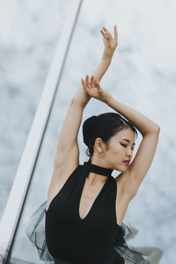 Beautiful woman with arms raised standing against building