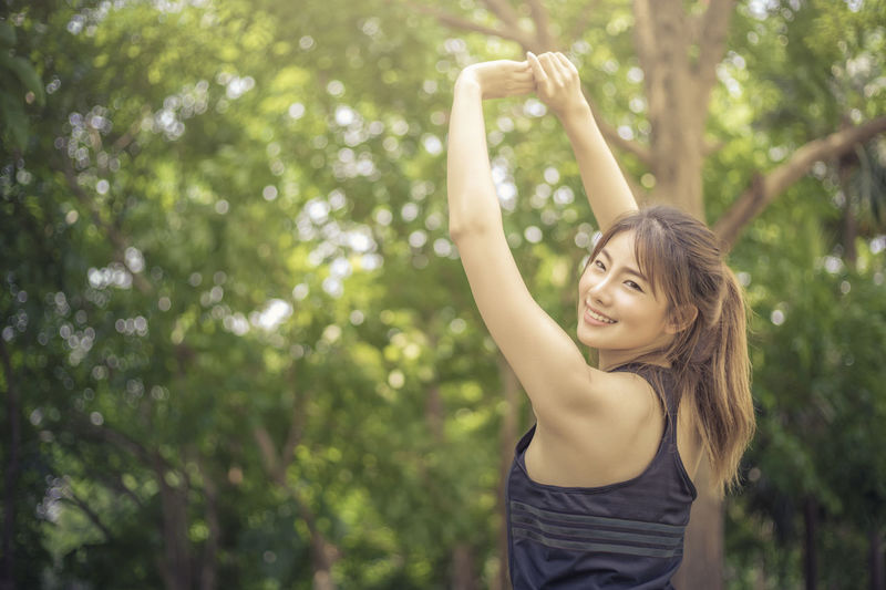 Portrait of young woman exercising against trees
