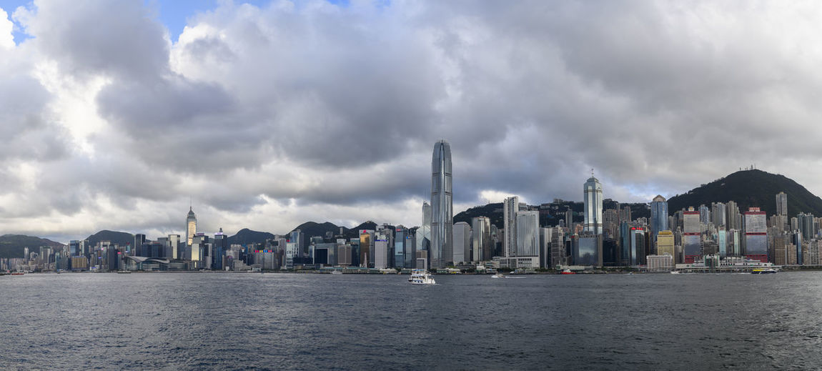 Panoramic view of sea by buildings against sky