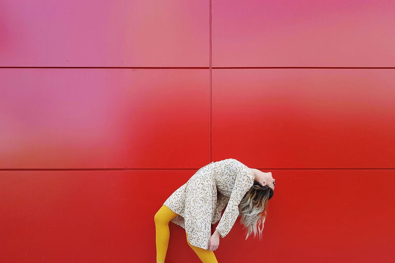 Side View Of Young Woman Bending By Red Wall