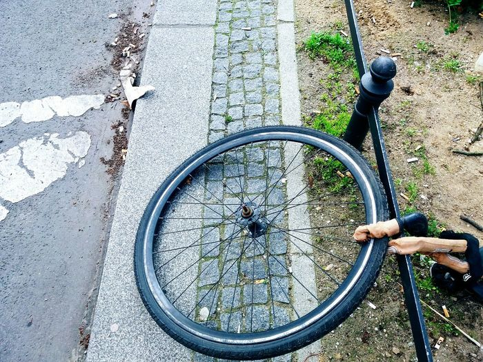 single wheel of a bike chained on a post Bicycle Street Outdoors Wheel Wheel Of A Bike Transportation