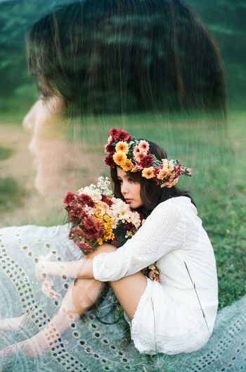 Double exposure of image depressed woman wearing flowers