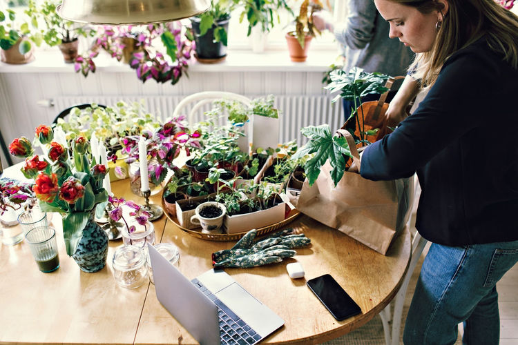 Midsection of woman standing by potted plants on table