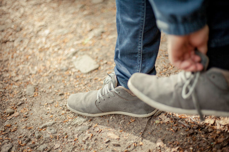Low section of person adjusting shoe while standing on field