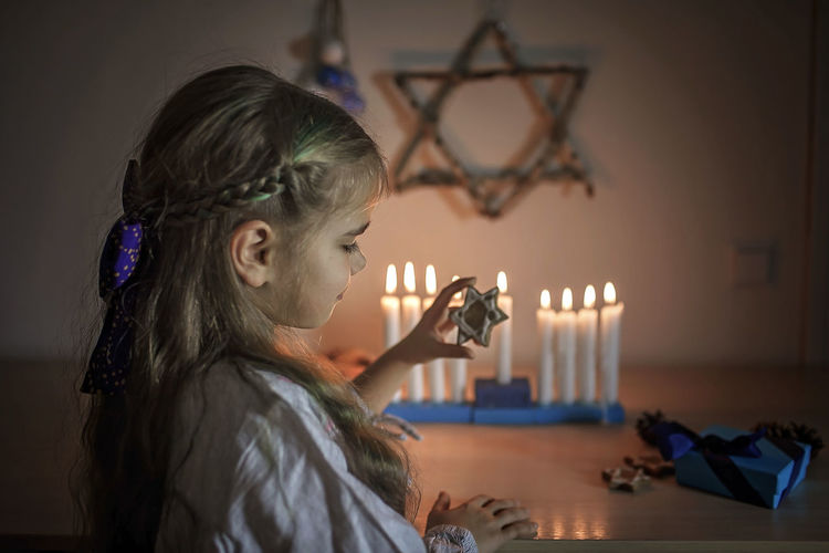 Cute girl holding star shape while standing against burning candles