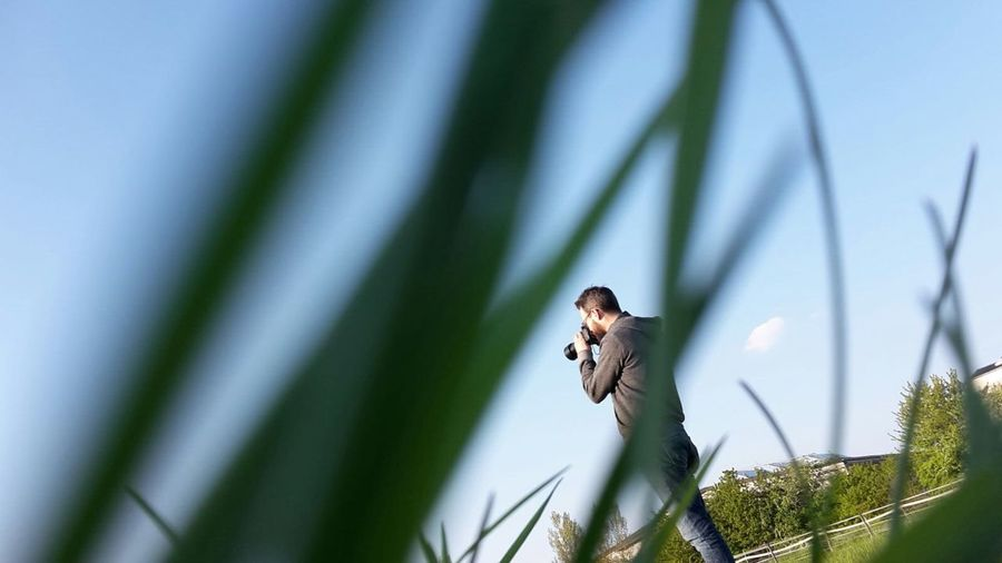 Rear View Of Man Photographing Through Digital Camera On Field