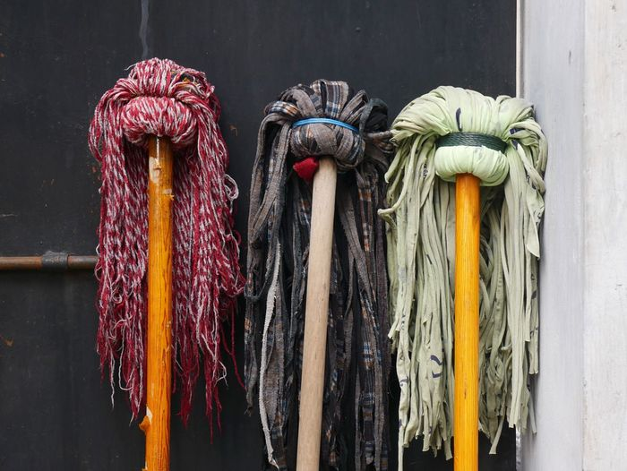 Close-up of mops by wall