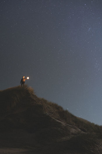 Low Angle View Of Young Man Standing On Mountain Against Star Field At Night