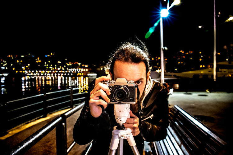 young man taking a photo in night, near sea. Camera - Photographic Equipment Photography Themes Photographing Technology Night Illuminated Front View Photographer Architecture One Person Holding Portrait Standing Photographic Equipment Activity Young Adult Looking At Camera City Real People Outdoors Digital Camera