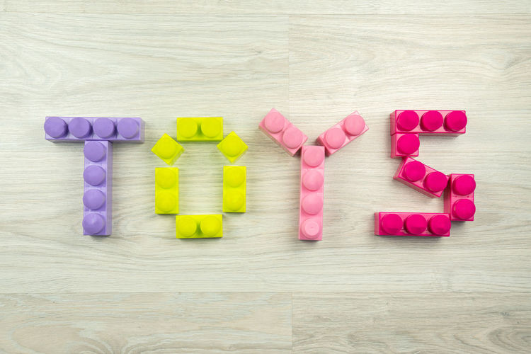 the word toys spelled with blocks, on a wooden background. Can be used as a background Multi Colored Still Life Table Pink Color Wood - Material Text Arrangement Close-up Large Group Of Objects High Angle View Variation Directly Above Toy Western Script Toys Blocks Wooden Background