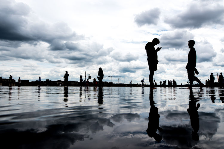 Silhouette people on water against sky in city
